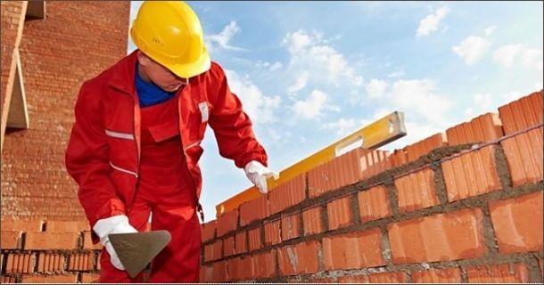 строитель выполняет кладку